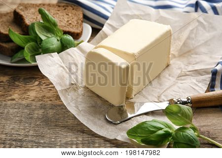 Piece of unwrapped butter and knife on wooden table