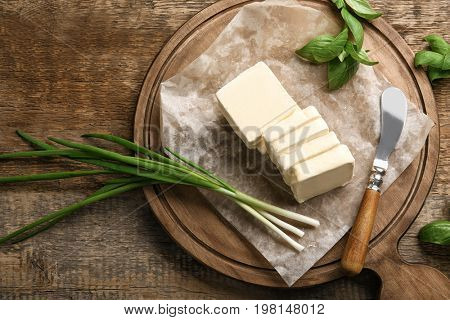 Cutting board with unwrapped sliced butter, knife and greens on wooden table