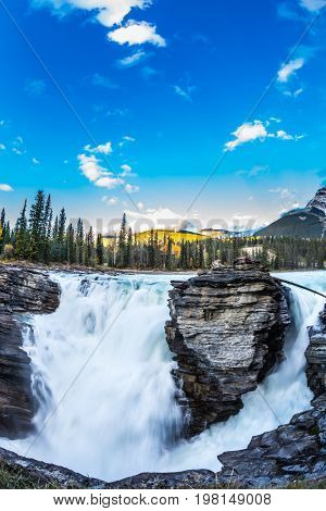 The bubbling waterfall of Athabasca. Clear evening in Jasper National Park. Cold blue water at sunset. The concept of extreme and ecological tourism