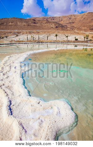 Reduced water in the salty Dead Sea, Israel.  The concept of medical and ecological tourism. The evaporated salt has developed into fantastic patterns
