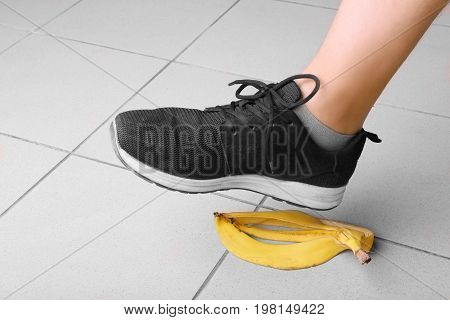Male's leg in black trainers slips on a banana peel, on a gray background. Bright yellow banana peel on the floor. Accident, danger and risk concept.