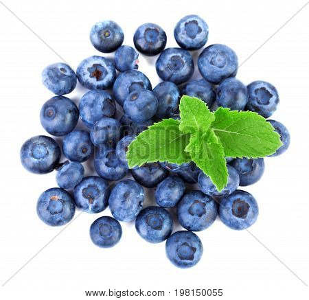 Top view of a lot of fresh and natural blueberries with green mint, isilated on a white background. Summer berries with mint full of vitamins, close-up. Healthful and sweet dark berries.