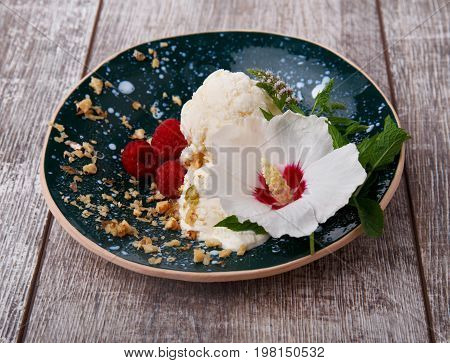 A colorful composition of sweet, cool, nutritious vanilla ice cream in a blue bowl on a light brown wooden background. Tasteful ice cream ball with pink raspberries, green mint and cute white flower.