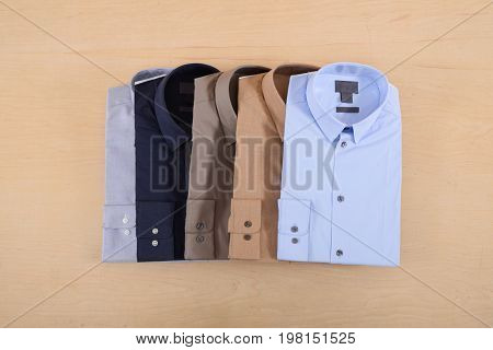Business classic men's five, shirts on wooden background