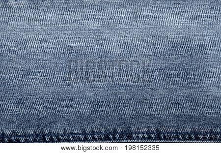 Closeup of denim jean texture with seam.