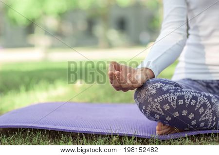 A close-up yoga lady sitting in a lotus position. A skinny sports girl sitting on a bright purple mat. Simple and painless asanas for beginners. Balance, peace, energy concept.