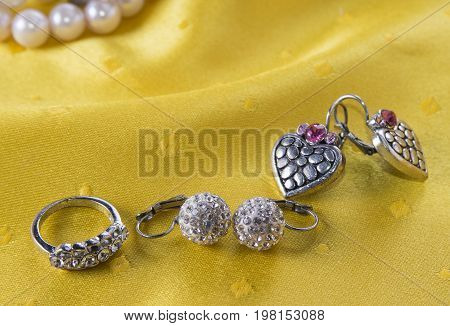 Two pairs of earings and ring on the yellow background