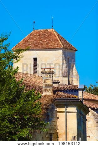 Roof of a French traditional house with a weathercock and a lightning rod on a beautiful blue sky