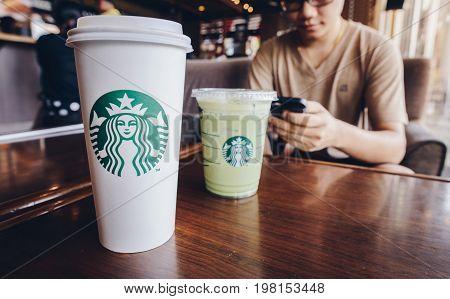 CHIANG RAI, THAILAND- JUNE 23, 2017 : A Venti Starbucks coffee and Grande Ice green tea latte in Starbucks coffee shop.
