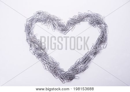 Heart make from paper clips ready to text to be write on white