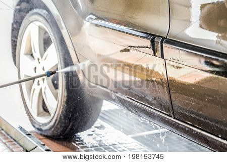 Cleaning car with high pressure water at carwash. vehicle concept
