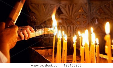 Jerusalem, Israel - May 25, 2017: Prayers lighting candles in the Holy Sepulcher Church in Jerusalem. The Holy Sepulchre Church and Empty Tomb the most sacred places for all Christians in the world.
