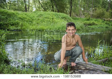 In summer a bright sunny day on the river bank sits a boy.