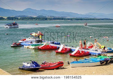 LiPTOVSKY TRNOVEC SLOVAKIA - AUGUST 2: People relaxing and sunbathing on shore of water reservoir Liptovska Mara. Summer sports at lake on August 2 2017 in Liptovsky Trnovec