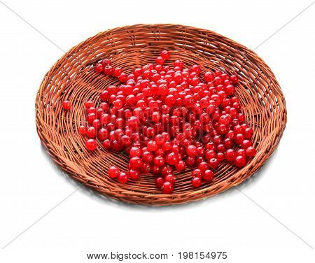 A view from above on a red currant in a wicker wooden basket, isolated on a white background. Juicy and sour red currants in a brown crate. Appetizing ingredients for vegan cocktails.
