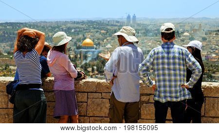 Jerusalem, Israel - May 25, 2017: The guide shows the Jerusalem Old City view to the tourists and pilgrims. Mount of Olives is a famous Holy Land place and it has a fantastic view to the Old Jerusalem