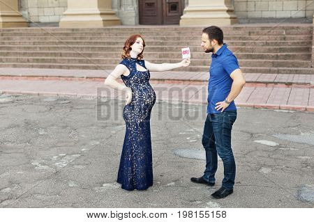 Funny image. Couple expecting a baby girl: pregnant mother holds a sign saying