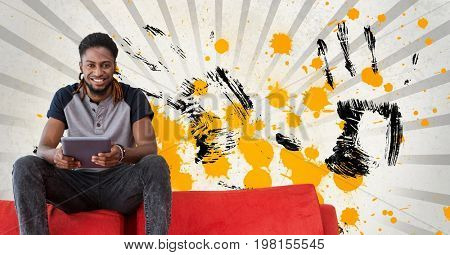 Digital composite of Happy young student man holding a tablet against grey, yellow and black splattered background