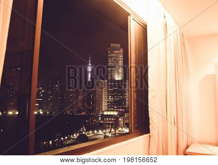 Spectacular night city view from hotel window. Kuala Lumpur skyscrapers, Malaysia. Business metropolis. Modern buildings. Luxurious travel and tourism. Urban cityscape. Metropolitan architecture. Blur