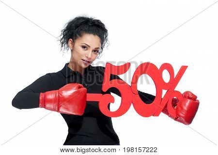 Beautiful brunette woman punching percentage sign wearing red boxing gloves price pricing discount sales seller retail shopping shopaholic consumerism concept.