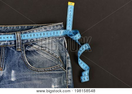 Dieting Concept: Denim Trousers With Measure Tape On Waist