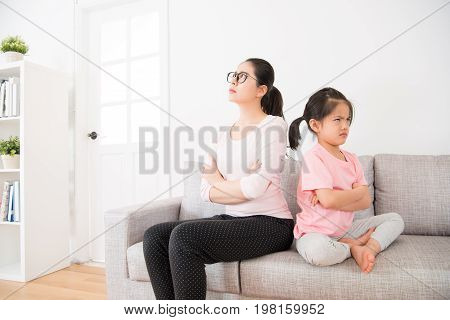 Mother And Daughter Back To Back Sitting On Sofa