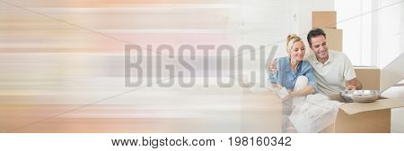 Digital composite of Happy couple opening boxes in their new house