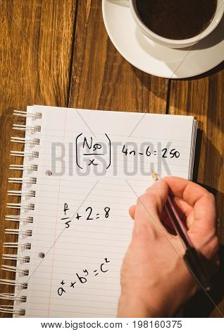 Digital composite of Hand writing math sums on notepad