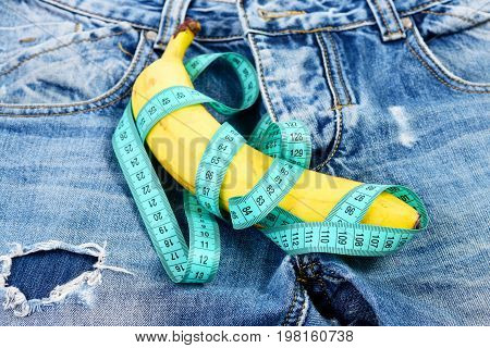 Jeans zipper and pocket close up. Mens denim pants crotch with banana imitating male genitals. Health and male sexuality concept. Banana wrapped with blue measure tape on jeans selective focus.