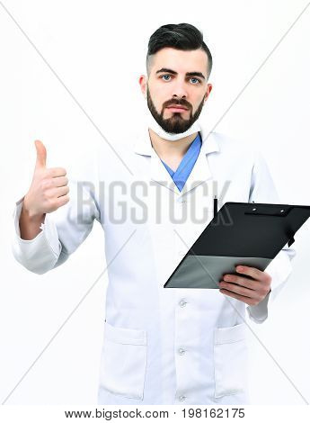 Physician in surgical mask isolated on white background. Doctor with beard holds clip folder for prescriptions and shows thumbs up. Man with serious face in white coat. Successful treatment concept