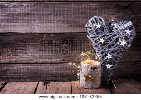 Decorative heart candleholder and fairy light on aged wooden background. Decorative christmas composition. Place for text.