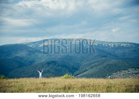 woman in field with mountains on background pictered from long distance in summer day