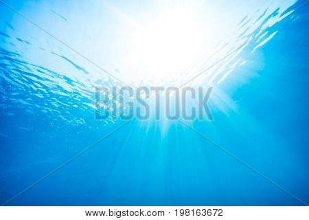 Beautiful view from underwater, sun rays through the surface of the water, underwater diving, blue water background