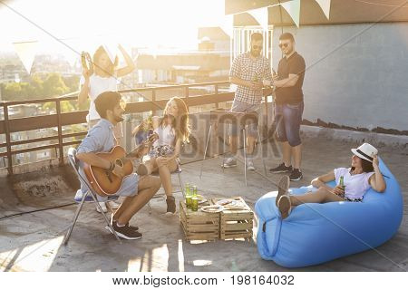 Group of young friends having fun at rooftop party making barbecue drinking beer playing the guitar and enjoying hot summer days. Focus on the girl sitting on the chair