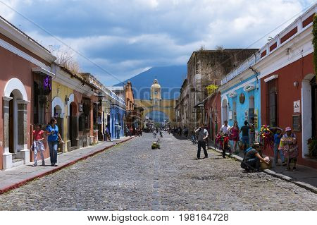 Antigua Guatemala - April 16 2014: View of a cobblestone street in the old city of Antigua with the Agua Volcano on the background in Guatemala