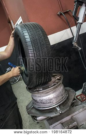 Car mechanic hands lubricating tire before mounting the rim. Installing wheel process poster