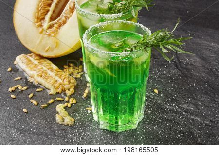 A beautiful composition of an alcohol drinks, lime and ripe melon on a black background. Bright green drinks in two glasses with tarragon. Fresh and natural cantaloupe and honeydew. Summer fruits.