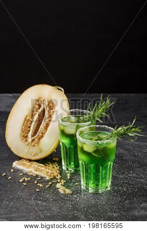 A couple of glasses full of non-alcohol and organic cold drinks and a cut in half cantaloupe melon on a black background. Juicy melon honeydew and sweet lime drinks with tarragon leaves on a table.