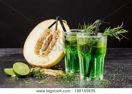 Two beautiful glasses of green drinks with ice and tarragon leaves and delicious cut melon on a black background. Refreshing and fruity alcoholic summer beverages. Fresh melon and cold cocktails.