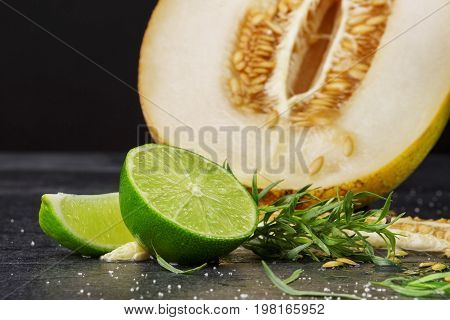 A close-up composition of a fresh melon with lime and tarragon on a black background.  Ripe cantaloupe and honeydew cut in a half with lime and tarragon leaves. A sweet cut melon and sour lime.