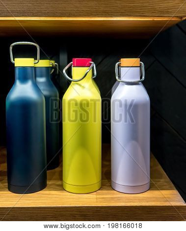Stainless Steel Vacuum Water Bottle With Twist Off Lid For Cold Beverages On Wooden Shelf.