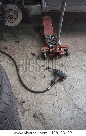 Changing car tire concept. Hydraulic car jack new tyres and pneumatic wrench screwing at garage