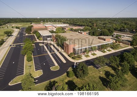 Aerial view of a high school with parking lot and ballfields in a suburban setting in Northbrook, IL