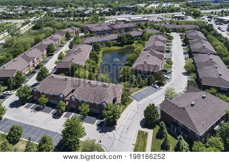 Aerial view of a townhouse complex with a small pond in a Chicago suburban neighborhood in summer.