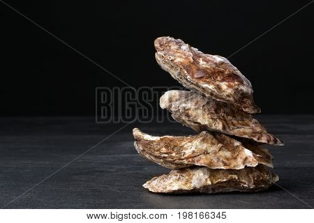 A small pile of four close juicy oysters on a black background. Fresh tropical sea mollusks full of nutrients. Close seashells. Expensive food. The greatest delicacy. Healthy food.