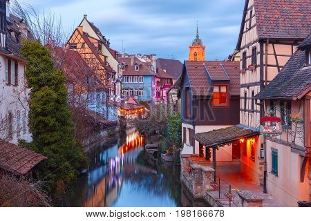 Traditional Alsatian half-timbered houses, church and river Lauch in Petite Venise or little Venice, old town of Colmar, decorated and illuminated at christmas time, Alsace, France