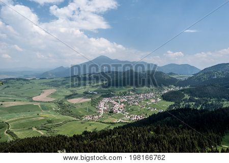 Komkatna village with nice countryside around and Chocske vrchy mountain range with Velky Choc hill on the background from Hrdosna skala hill in Velka Fatra mountains in Slovakia