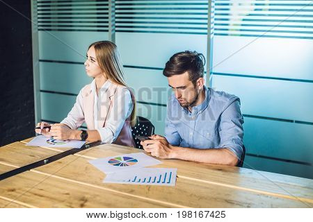 Boring presentation. Group of young business people in smart casual wear looking bored while sitting together at the table and looking away.