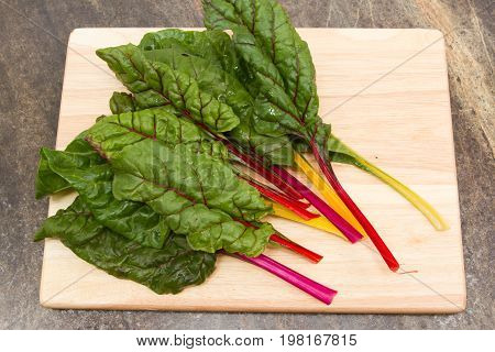 Swiss chard home grown organic swiss chard on a wooden board