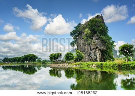 Scenic Karst Tower Reflected In Water Of The Ngo Dong River